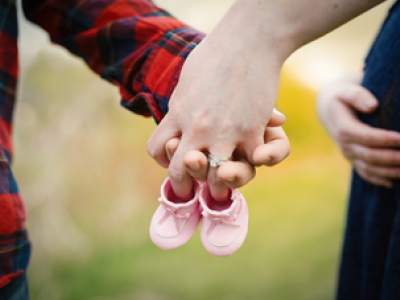 Couple expecting a baby girl as signified by the pink booties